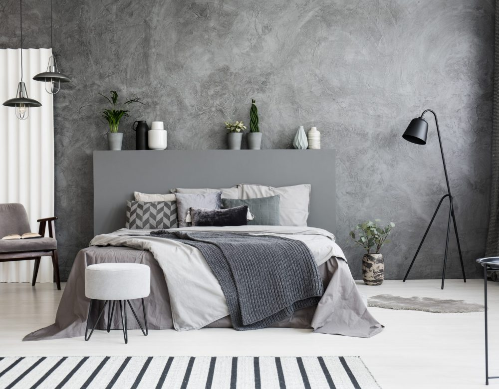 grey-armchair-and-stool-near-bed-with-headboard-in-JGXBRKQ-scaled.jpg